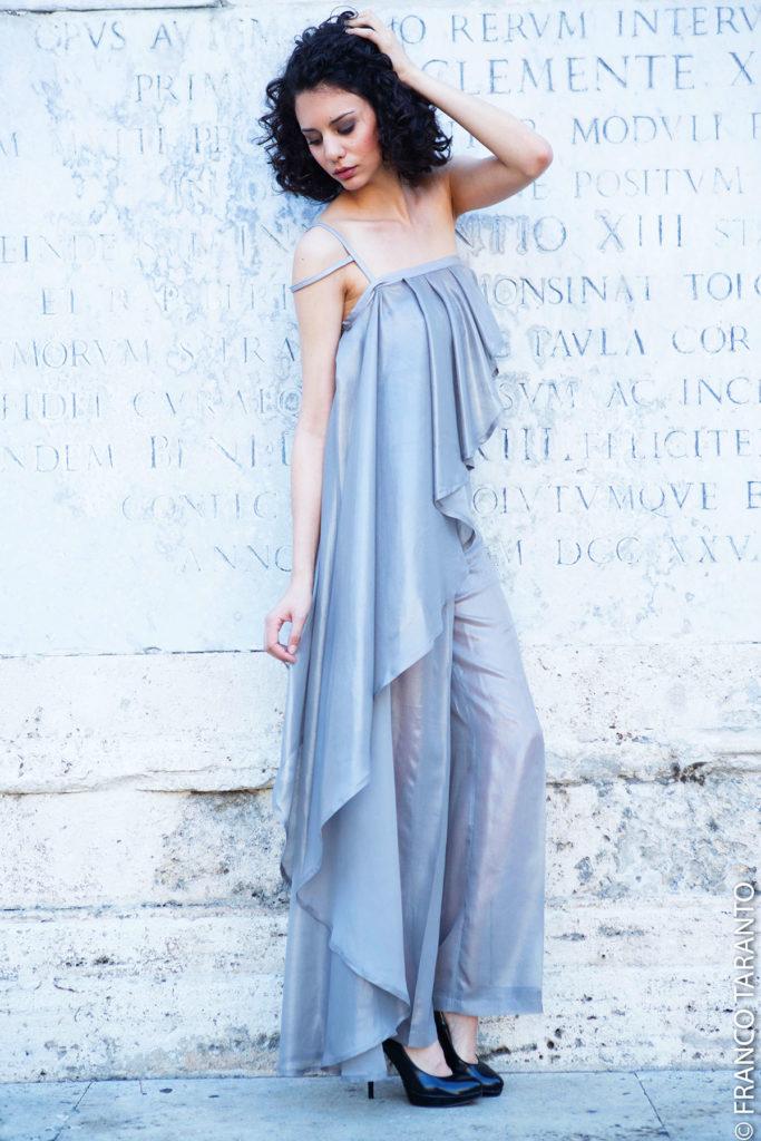 Completo da sera in georgette di seta cangiante composto da un velo asimmetrico drappeggiato. Body a uncinetto e pantalone dritto.