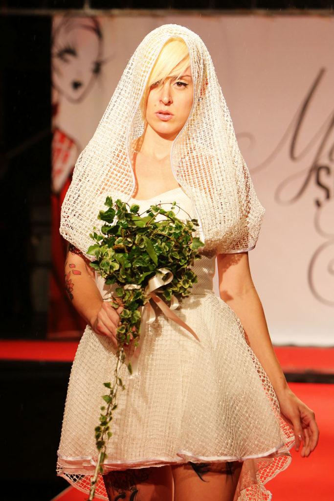 Vestito da sposa, body in fina lana con pantaloncino. Gonna voluminosa con strascico corto e cintura ampia in fina lana con cappuccio integrato.