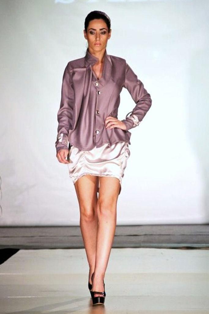Giacca in fina lana con drappeggio asimmetrico. Minigonna in raso di seta con plissettature.