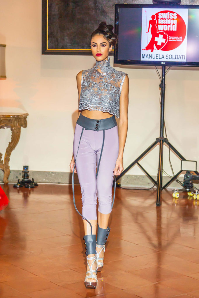 Completo streetwear, top corto in pizzo grigio, legging di lycra con lacci cintura in ecopelle.