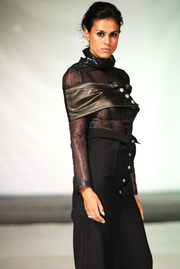 Top a maniche lunghe in organza di seta, ampia cintura in ecopelle lucido. Pantalone palazzo a taglia impero, stampa gessato in fina lana.