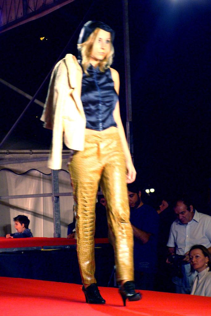 Top con cappuccio plissettato in raso di seta. Giacca in jacquard di lino. Pantalone dritto in ecopelle effetto coccodrillo.